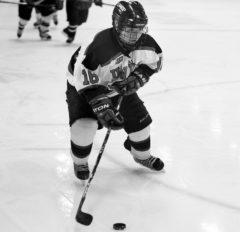 Kait Mason, senior forward, handles the puck in a women's hockey game.
