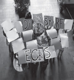 Members of the UW-River Falls ECOS club hold signs on 2015 Global Divestment Day in the University Center.