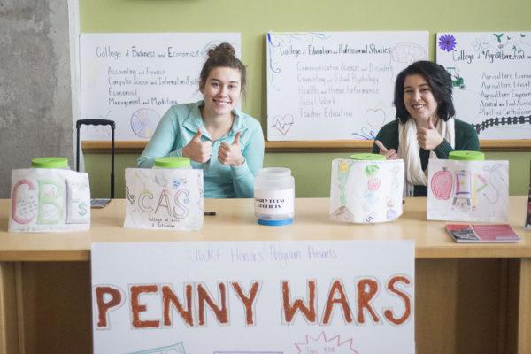 Marissa Koller (left), a junior and Adrianna Erickson, man the Penny Wars table in the University Center, Dec. 6. Photo by Tori Schneider/Student Voice