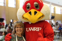Mary Van Galen poses with Freddy the Falcon during the Relay for Life event at the River Falls High School last Friday.